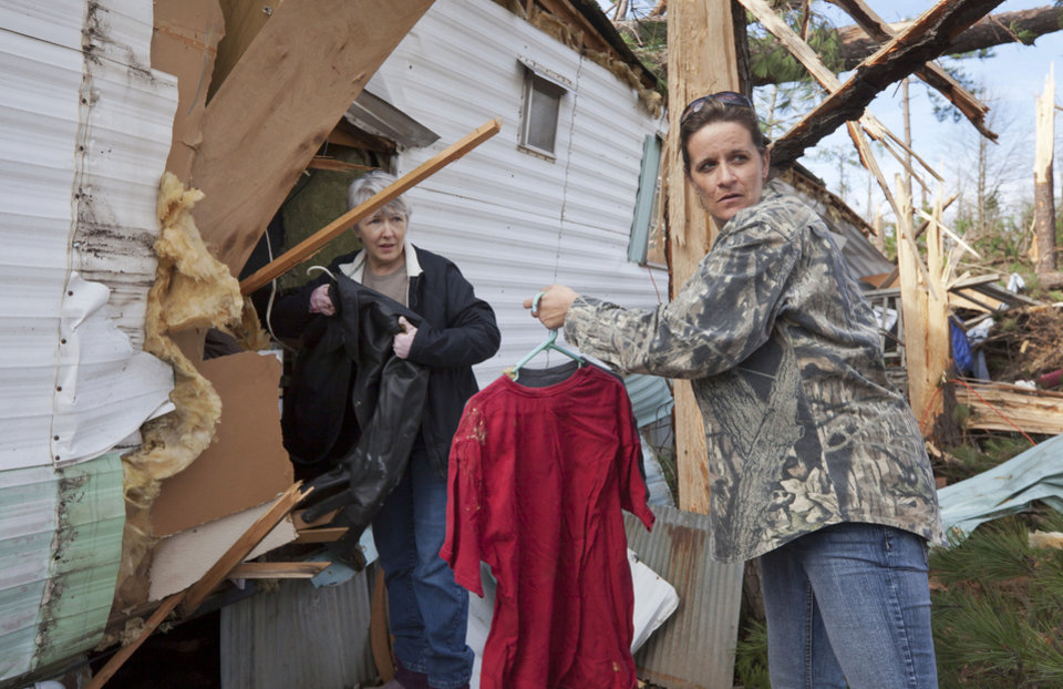 Lou Ann Sherman, right, and Sandra Lloyd salvage clothing from a storm-damaged mobile home belonging to their friend in Fordyce, Ark., Monday, Jan. 23, 2012. (AP Photo/Danny Johnston) ORG XMIT: ARDJ101