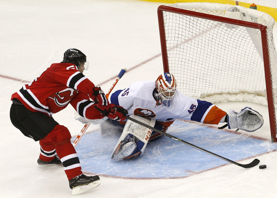 Photo - New Jersey Devils right wing Jaromir Jagr, left, of the Czech Republic, misses a shot against New York Islanders goalie Anders Nilsson, of Sweden, during a shootout in an NHL hockey game, Friday, April 11, 2014, in Newark, N.J. The Islanders won 3-2. (AP Photo/Julio Cortez)