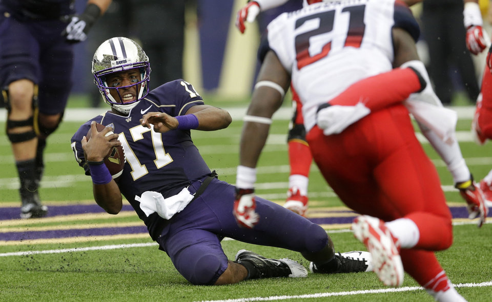 Photo - Washington quarterback Keith Price (17) slides after keeping the ball in the first half of an NCAA college football game against Arizona, Saturday, Sept. 28, 2013, in Seattle. (AP Photo/Ted S. Warren)
