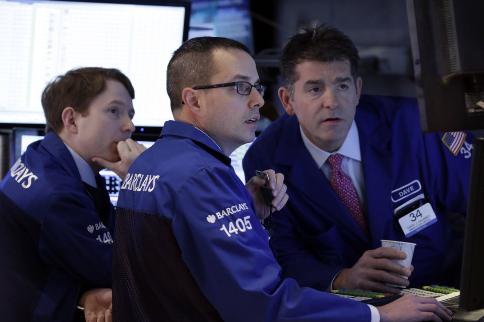 Photo -  Specialists Peter Elkins, Neil Gallagher and David Haubner, left to right, work Monday on the floor of the New York Stock Exchange. Global stock markets are down sharply on tensions over Russia's military advance into Ukraine and the threat of sanctions by Western governments. AP photo   Richard Drew -