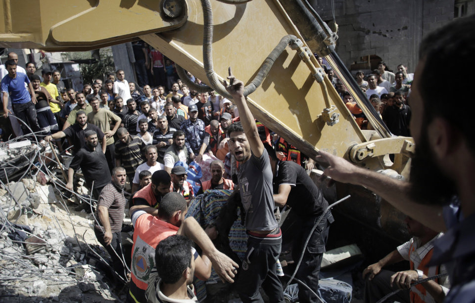Photo - A Palestinian man chants angry slogans as rescue workers search for victims under the rubble of a house destroyed in Israeli strikes in the Rafah refugee camp, Southern Gaza Strip, Thursday, Aug. 21, 2014. (AP Photo/Khalil Hamra)