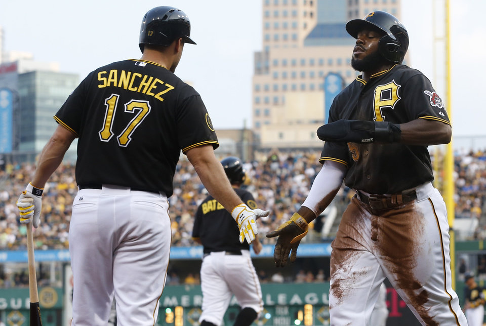 Photo - Pittsburgh Pirates' Josh Harrison (5) is greeted by on deck batter Gaby Sanchez (17) after scoring on a hit by Russell Martin in the first inning of a baseball game against the San Diego Padres on Saturday, Aug. 9, 2014, in Pittsburgh. (AP Photo/Keith Srakocic)