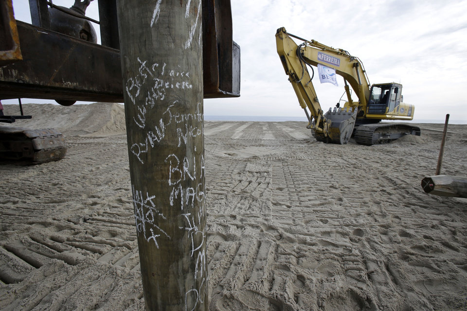 Photo - The first piling of the new boardwalk construction has signatures of officials  Wednesday, Jan. 9, 2013, in Belmar, N.J., as officials kick off the construction on a 1.3-mile boardwalk to replace the walkway destroyed by Superstorm Sandy in October. The goal is to have it done by May. (AP Photo/Mel Evans)