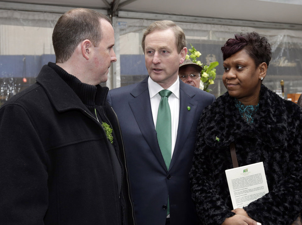 Photo - Irish Prime Minister Enda Kenny, right, meets with Damien and Glenda Moore, of Brooklyn, N.Y., at the 17th annual Ireland Chamber of Commerce St. Patrick's Day Breakfast, in New York,  Saturday, March 16, 2013. The couple lost their two young sons who were swept from their mother's arms by the violent sea at the height of Superstorm Sandy. (AP Photo/Richard Drew)
