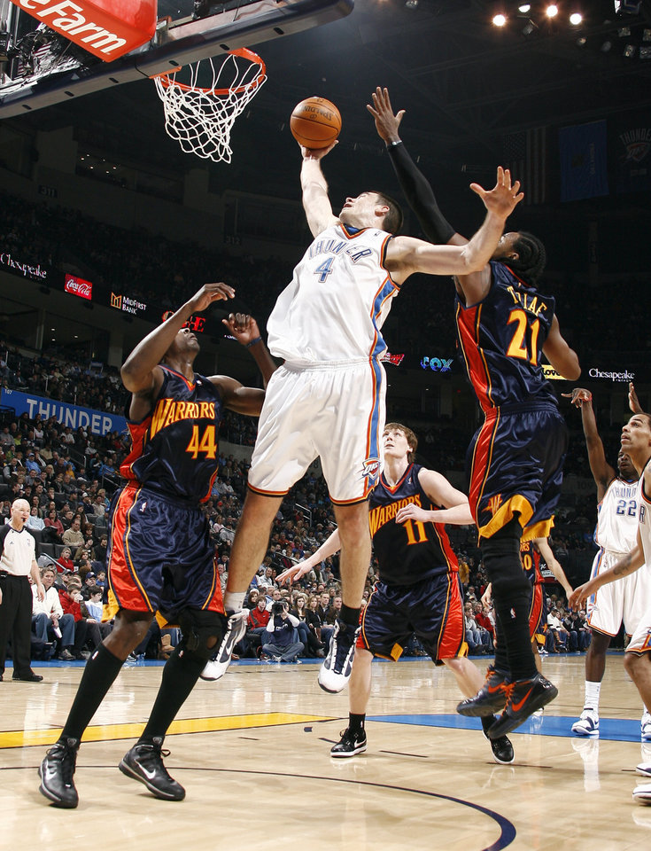 Photo - Oklahoma City's Nick Collison (4) grabs a rebound in front of Golden State's Anthony Tolliver (44), Coby Karl (11) and Ronny Turiaf during the NBA game between the Oklahoma City Thunder and Golden State Warriors, Sunday, Jan. 31, 2010, at the Ford Center in Oklahoma City. Photo by Sarah Phipps, The Oklahoman