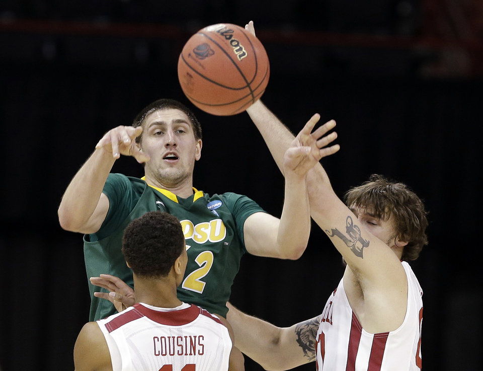 Photo - North Dakota State's Marshall Bjorklund passes between Oklahoma players in the first half during a second-round game of the NCAA men's college basketball tournament, in Spokane, Wash., Thursday, March 20, 2014. (AP Photo/Elaine Thompson)