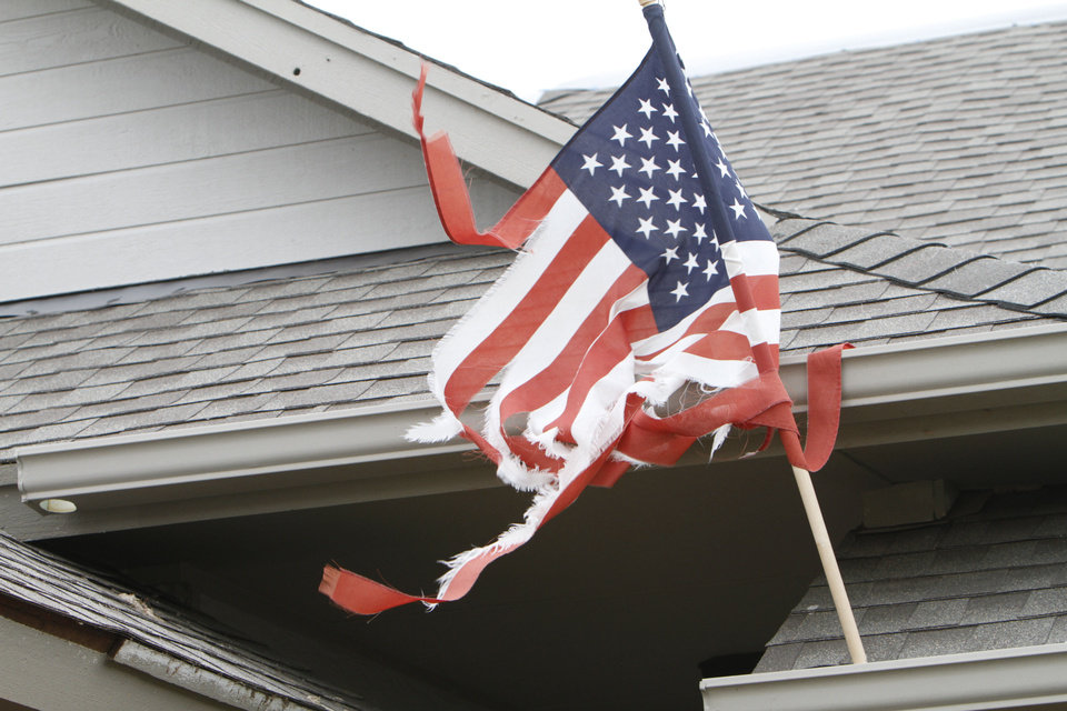 WESTMOOR HOUSING ADDITION / TORNADO DAMAGE / TORNADO AFTERMATH / CLEANUP: A tattered American flag, still attached to a damaged home in the Westmoor neighborhood in southwest Oklahoma City,  blows in the wind Thursday, May 30, 2013. Photo by Aliki Dyer, The Oklahoman <strong>Aliki Dyer - The Oklahoman</strong>