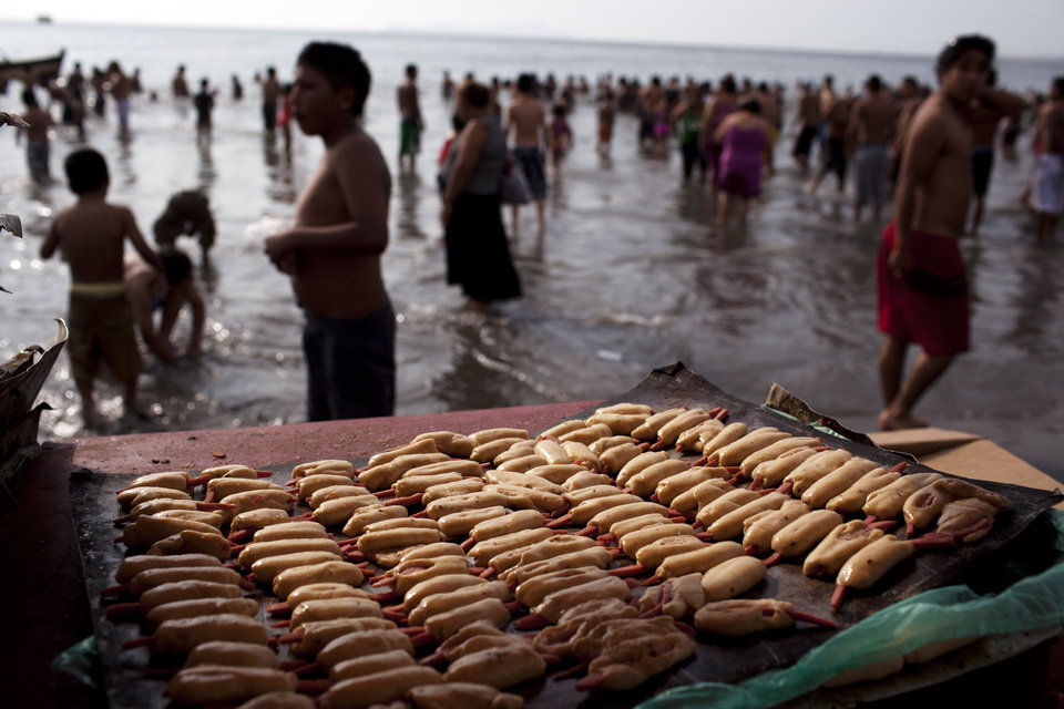 "In this Jan. 13, 2013 photo, uncooked bread covered sausage called ""Caramandunga,"" cooked on the spot for clients in a small portable oven, are display on Agua Dulce beach in Lima, Peru. While Lima's elite spends its summer weekends in gate beach enclaves south of the Peruvian capital, the working class jams by the thousands on a single municipal beach of grayish-brown sands and gentle waves. The only barrier to entry to ""Agua Dulce"" beach is two dollars, the price of bus fare to get there and home. (AP Photo/Rodrigo Abd)"