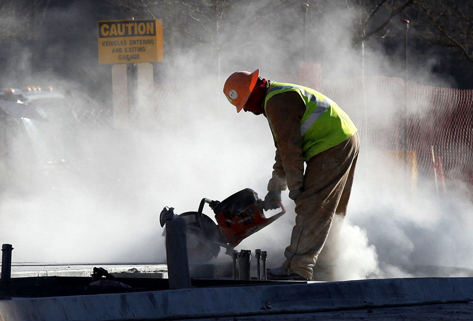 A construction worker stands in a cloud of dust as he saws expansion joints into new sidewalks along Harvey Avenue in downtown Oklahoma City, OK, Tuesday, Jan. 18, 2011. By Paul Hellstern, The Oklahoman