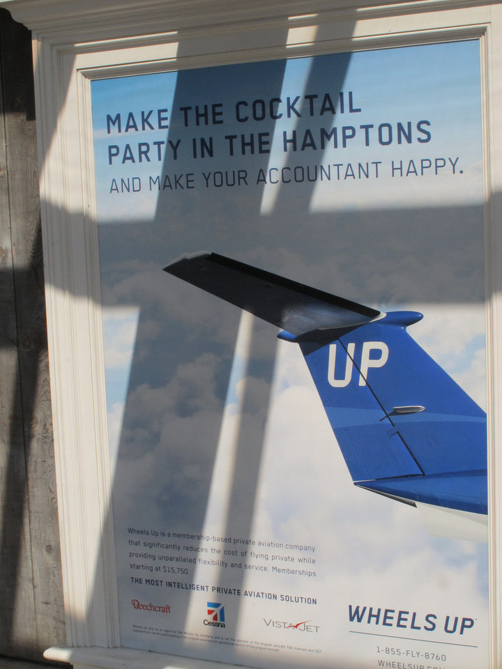 Photo - In this Aug. 20, 2014 photo, an advertisement for a private air company welcomes visitors to the East Hampton Town Airport. Residents across eastern Long Island are complaining about the noise generated from jets, helicopters and other aircraft that land at the small municipal airport, which is situated in the heart of the summer playground for the rich and famous. (AP Photo/Frank Eltman)