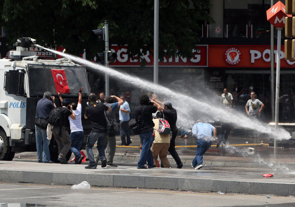 Photo - Turkish riot police spray water cannon at demonstrators who remained defiant after authorities evicted activists from an Istanbul park, making clear they are taking a hardline against attempts to rekindle protests that have shaken the country, in city's main Kizilay Square in Ankara, Turkey, Sunday, June 16, 2013.(AP Photo/Burhan Ozbilici)