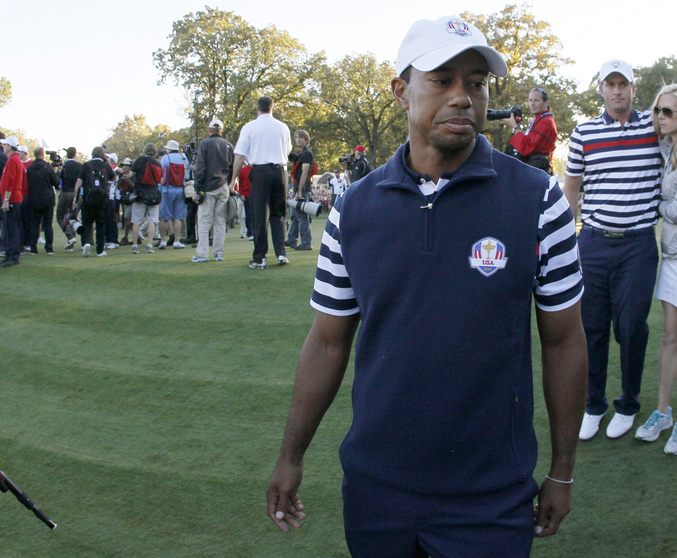 Photo - USA's Tiger Woods walks off the course as Europe celebrates their win at the Ryder Cup PGA golf tournament Sunday, Sept. 30, 2012, at the Medinah Country Club in Medinah, Ill. (AP Photo/Charles Rex Arbogast)  ORG XMIT: PGA210