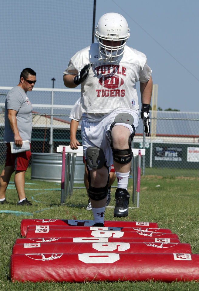 Photo - Zaine Bates  goes through drills during high school football practice on Tuesday, Aug. 12, 2014 in Tuttle, Okla. Photo by Steve Sisney, The Oklahoman