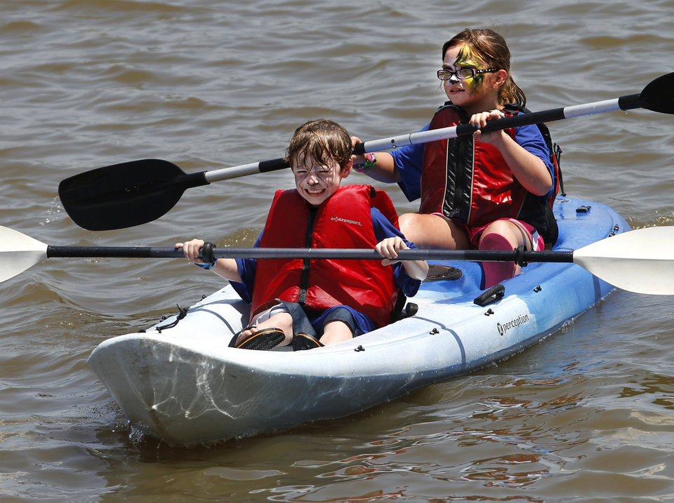 Harrison Griffin, 6, front, and Tyler Berkeley, 8, paddle a kayak back to shore at the Stars and Stripes River Festival on the Oklahoma River, Saturday afternoon, June 30, 2012.  Photo by Jim Beckel, The Oklahoman