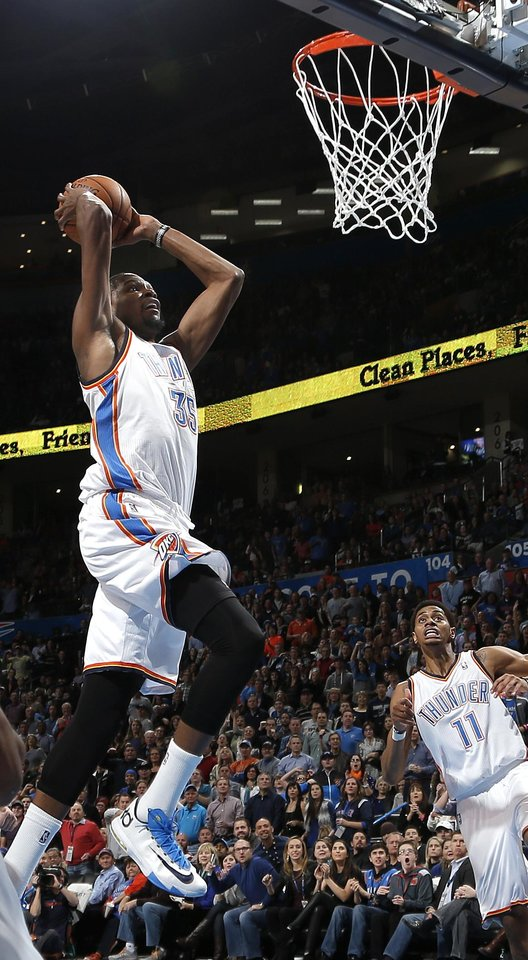 Photo - Oklahoma City's Kevin Durant (35) goes up for a dunk during the NBA game between the Oklahoma City Thunder and the Golden State Warriors at the Chesapeake Energy Arena, Friday, Nov. 29, 2013. Photo by Sarah Phipps, The Oklahoman