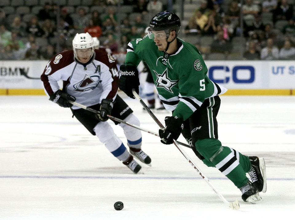 Photo - Dallas Stars defenseman Jamie Oleksiak (5) moves the puck as Colorado Avalanche left wing Alex Tanguay (40) pressures in the second period of a preseason NHL hockey game on Thursday, Sept. 26, 2013, in Dallas. (AP Photo/Tony Gutierrez)