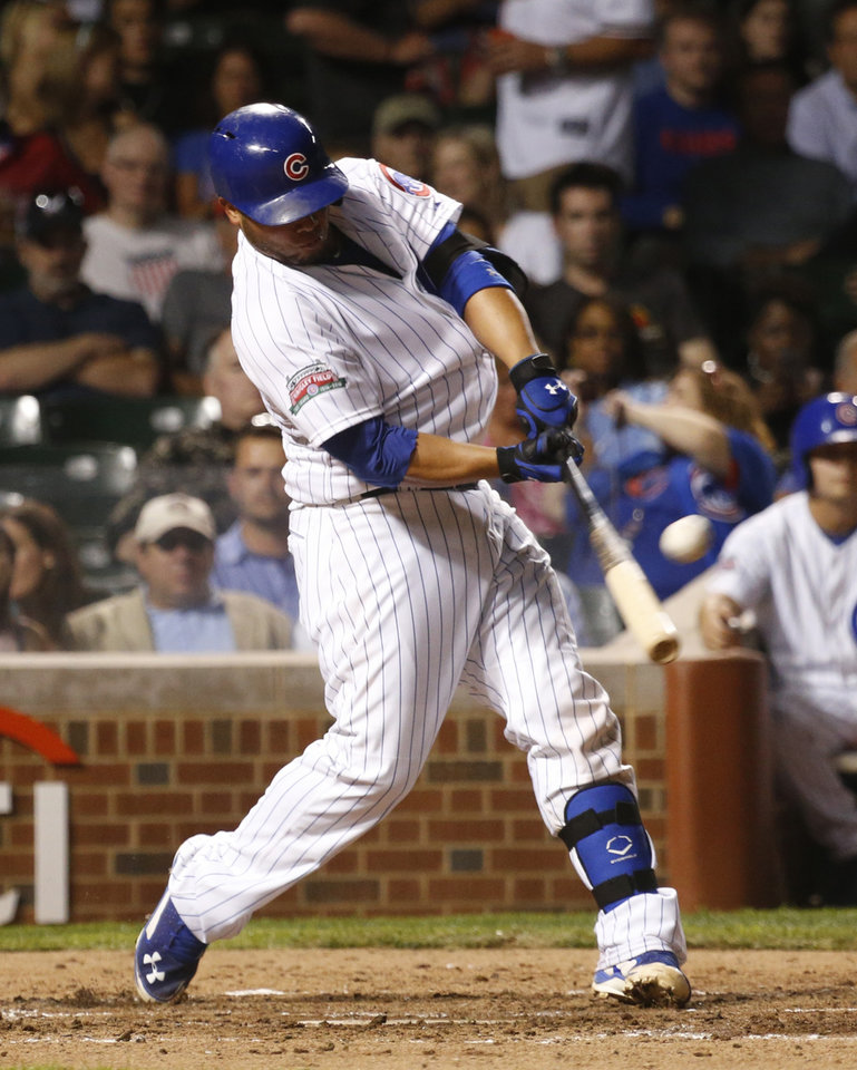 Photo - Chicago Cubs' Welington Castillo hits an RBI ground-rule double off Milwaukee Brewers starting pitcher Matt Garza during the third inning of a baseball game Wednesday, Sept. 3, 2014, in Chicago. (AP Photo/Charles Rex Arbogast)