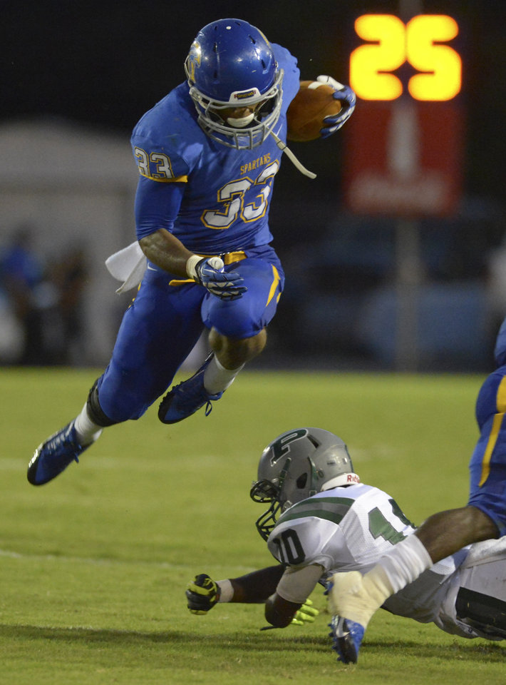 Photo - Advocate staff photo by HEATHER MCCLELLAND --  East Ascension's Sione Palelei escapes tackle by leaping over Plaquemine's Chazz Edwards during their game on Friday in Spartan Stadium in Gonzales.