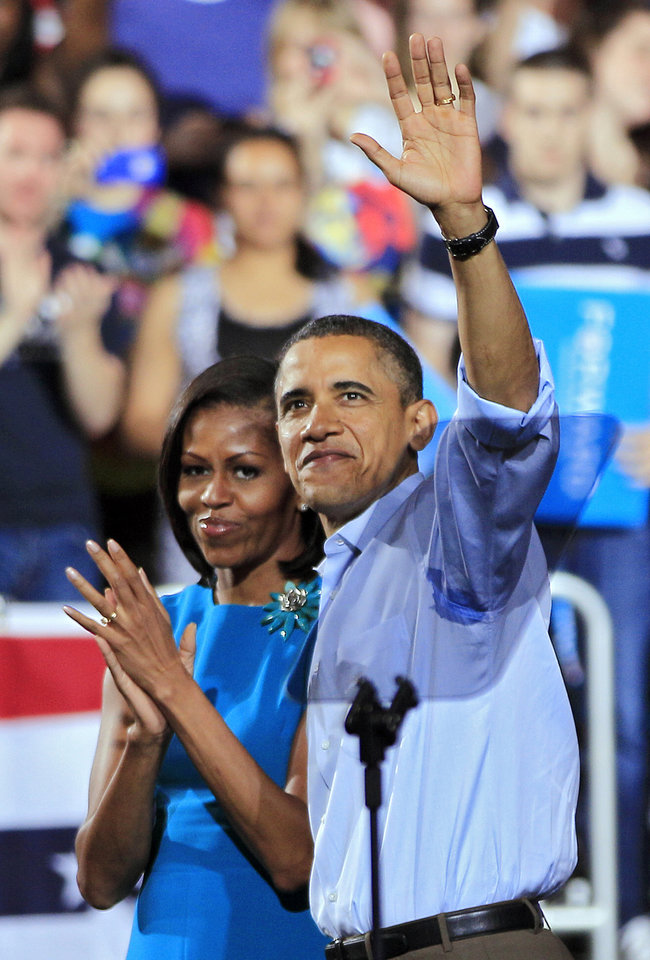 Photo -   President Barack Obama waves with first lady Michelle Obama after a campaign rally at The Ohio State University in Columbus, Ohio, Saturday, May 5, 2012. (AP Photo/Mark Duncan)