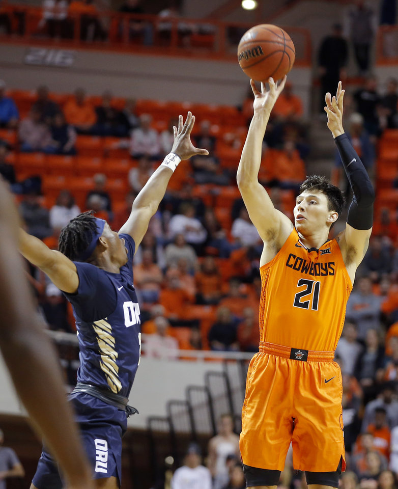 Photo - Oklahoma State's Lindy Waters III (21) makes a basket over Oral Roberts' Deondre Burns (2) during an NCAA basketball game between the Oklahoma State University Cowboys (OSU) and the Oral Roberts Golden Eagles (ORU) at Gallagher-Iba Arena in Stillwater, Okla., Wednesday, Nov. 6, 2019. [Bryan Terry/The Oklahoman]