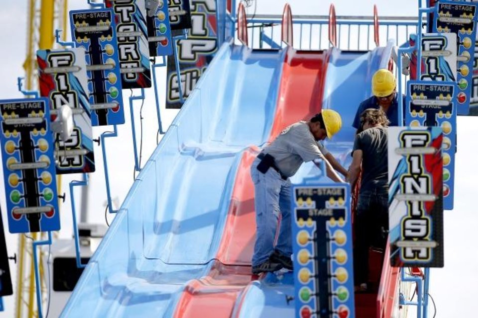 Photo -  Workers make adjustments to a slide for the Oklahoma State Fair at the OKC Fairgrounds in Oklahoma City, Tuesday, Sept. 10, 2019. [Bryan Terry/The Oklahoman]