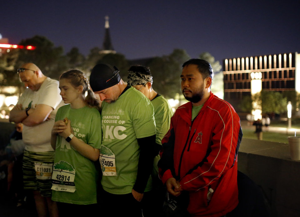 Photo - People pray during the Sunrise Service at the  Survivor Tree before during Oklahoma City Memorial Marathon in Oklahoma City, Sunday, April 28, 2019. [Sarah Phipps/The Oklahoman]