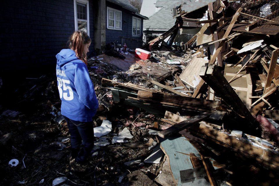 Photo -   Kate Traina, 14, looks over the rumble of her grandparents house in Staten Island, N.Y., Friday, Nov. 2, 2012. Mayor Michael Bloomberg has come under fire for pressing ahead with the New York City Marathon. Some New Yorkers say holding the 26.2-mile race would be insensitive and divert police and other important resources when many are still suffering from Superstorm Sandy. The course runs from the Verrazano-Narrows Bridge on hard-hit Staten Island to Central Park, sending runners through all five boroughs. The course will not be changed, since there was little damage along the route. (AP Photo/Seth Wenig)
