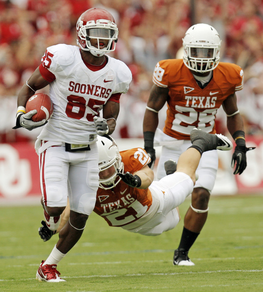 Photo - OU's Ryan Broyles (85) leaves behind Blake Gideon (21) and Quandre Diggs (28) after a catch in the first half during the Red River Rivalry college football game between the University of Oklahoma Sooners (OU) and the University of Texas Longhorns (UT) at the Cotton Bowl in Dallas, Friday, Oct. 7, 2011. Photo by Nate Billings, The Oklahoman