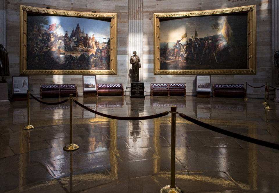 Photo - Normally filled with visitors and tourists, the empty Rotunda at the U.S. Capitol is seen in Washington, Tuesday, Oct. 1, 2013, after officials suspended all organized tours of the Capitol and the Capitol Visitors Center as part of the government shutdown. A statue of President Gerald R. Ford at center is illuminated amid large paintings illustrating the history of the United States. (AP Photo/J. Scott Applewhite)