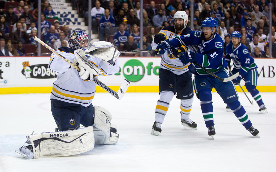 Photo - Buffalo Sabres' goalie Nathan Lieuwen, left, makes a glove save as Mike Weber, centre, defends while Vancouver Canucks' Henrik Sedin, of Sweden, looks for the rebound during first period NHL hockey action in Vancouver, British Columbia, on Sunday March 23, 2014. (AP Photo/The Canadian Press, Darryl Dyck)
