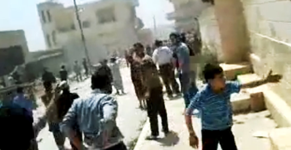 Photo -   In this image made from amateur video released by the Shaam News Network and accessed Tuesday, May 15, 2012, purports to show Syrians running from gun shots in Khan Sheikhoun, Idlib, Syria. A team of international observers were evacuated Wednesday from a tense town in northern Syria a day after their convoy was hit by a roadside bomb, a U.N. spokesman said. The team's vehicles were struck by the blast Tuesday during a mission in the northern town of Khan Sheikhoun. (AP Photo/Shaam News Network via AP video) TV OUT, THE ASSOCIATED PRESS CANNOT INDEPENDENTLY VERIFY THE CONTENT, DATE, LOCATION OR AUTHENTICITY OF THIS MATERIAL