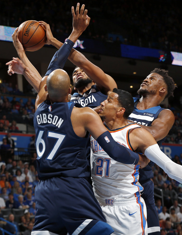 Photo - Minnesota's Karl-Anthony Towns (32) grabs a rebound next to Taj Gibson (67), Jimmy Butler (23) and Oklahoma City's Andre Roberson (21) during an NBA basketball game between the Oklahoma City Thunder and the Minnesota Timberwolves at Chesapeake Energy Arena in Oklahoma City, Sunday, Oct. 22, 2017. Photo by Nate Billings, The Oklahoman