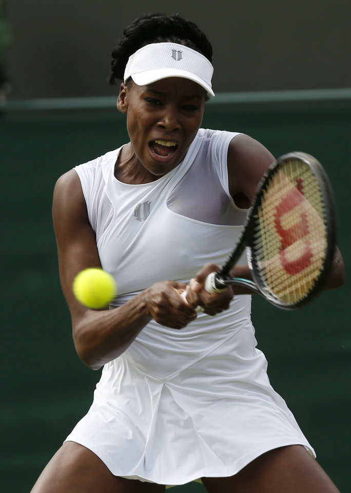 Photo - Venus Williams of the U.S. plays a return to Maria-Teresa Torro-Flor of Spain during their first round match at the All England Lawn Tennis Championships in Wimbledon, London,  Monday, June  23, 2014. (AP Photo/Sang Tan)