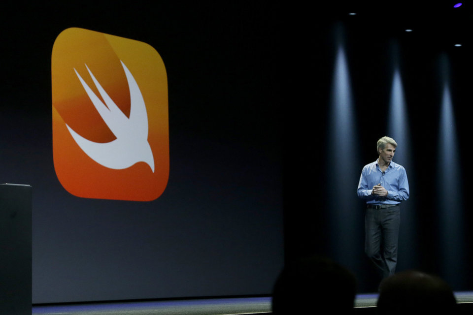 Photo - Apple senior vice president of Software Engineering Craig Federighi walks next to a symbol for Swift, a new programming language, while speaking at the Apple Worldwide Developers Conference in San Francisco, Monday, June 2, 2014. (AP Photo/Jeff Chiu)