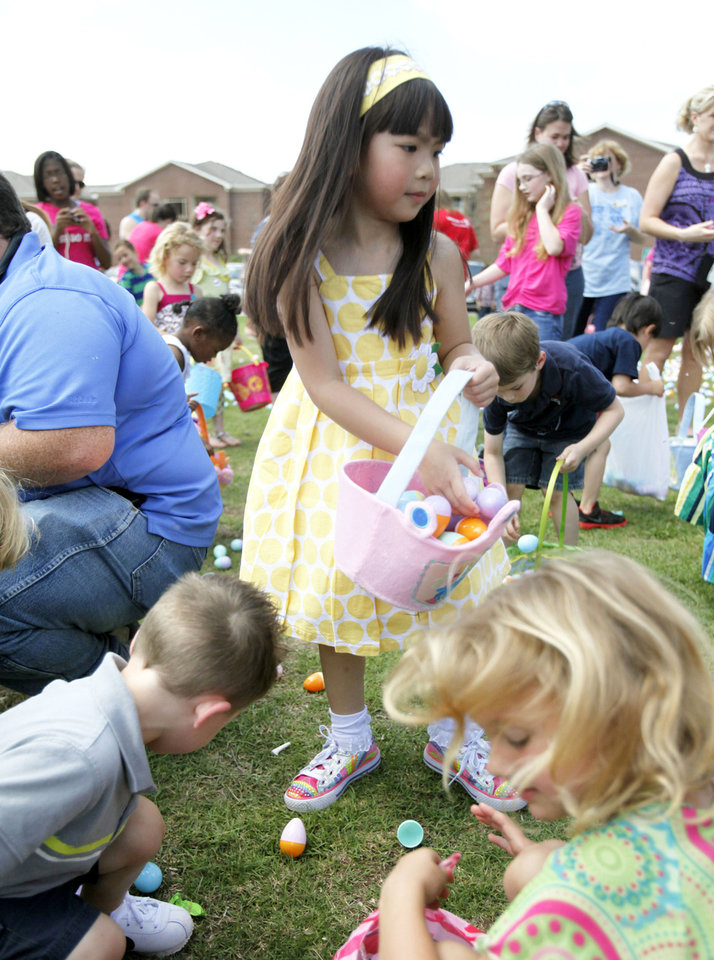 Kylie Phu, 5, fills her basket with eggs at an Easter egg hunt and carnival at University of Central Oklahoma in Edmond.   Photo By Paul Hellstern, The Oklahoman