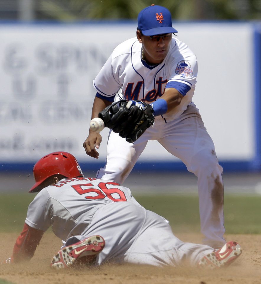 Photo - St. Louis Cardinals' Adron Chambers, bottom, is safe at second for a two-run double as the throw gets away from New York Mets shortstop Ruben Tejada during the fifth inning of an exhibition spring training baseball game Friday, March 29, 2013, in Port St. Lucie, Fla. (AP Photo/Jeff Roberson)