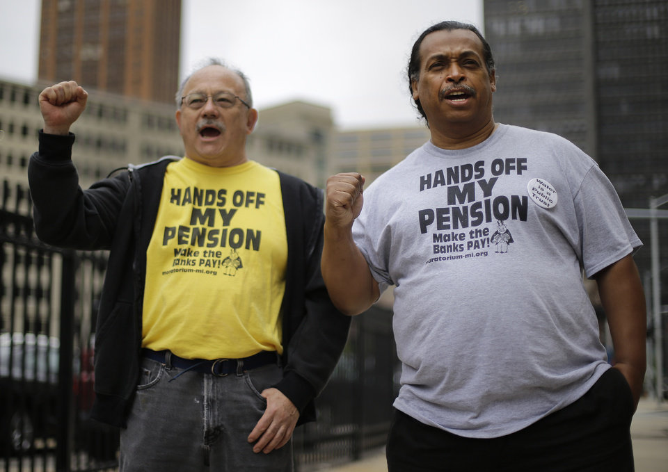 Photo - FILE - In a Thursday, July 3, 2014 file photo, Detroit retirees Mike Shane, left, and William Davis protest near the federal courthouse in Detroit on July 3, 2014. Ballots submitted by city workers, retirees, pensioners and other creditors likely will determine how quickly Detroit exits its historic bankruptcy. A major piece of the bankruptcy puzzle could fall into place Monday, July 21, 2014, with the expected release of the results of a vote by creditors, including more than 30,000 retired and current city workers, on whether to accept millions of dollars in cuts. (AP Photo/Paul Sancya, File)