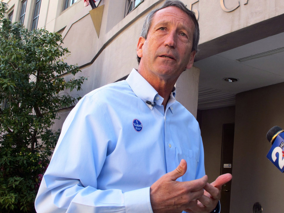 Photo - Former South Carolina Gov. Mark Sanford answers questions from reporters after voting in Charleston, S.C., on Tuesday, April 2, 2013. Sanford is facing former Charleston County councilman Curtis Bostic in the Republican runoff for South Carolina's vacant 1st District congressional seat.  (AP Photo/Bruce Smith)