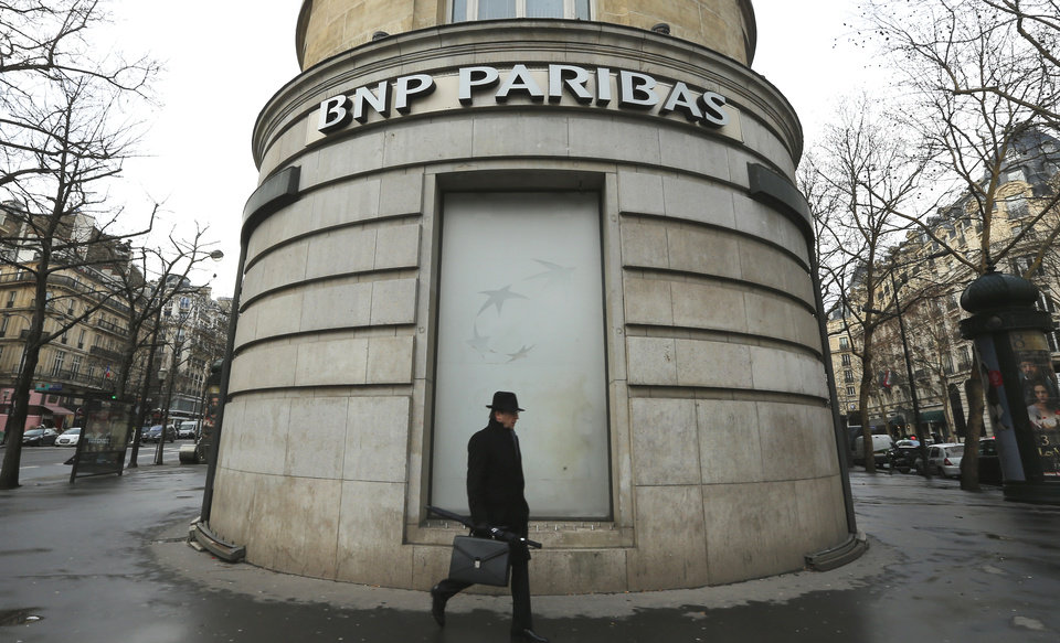 Photo - FILE - In this Feb. 5, 2013 file photo, a man walks past the French bank BNP Paribas headquarters in Paris. French economy minister Arnaud Montebourg on Monday, June 23, 2014 is urging U.S. authorities to be