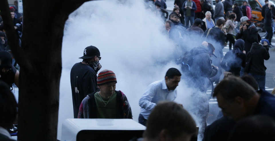 Potesters react after police set up a flash-bang grenade and tear-gas bombs during a May Day march that began as an anti-capitalism protest and turned into demonstrators clashing with police lies on the ground next to police batons, Wednesday, May 1, 2013, in downtown Seattle. (AP Photo/Ted S. Warren)