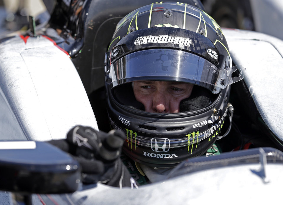 Photo - Race driver Kurt Busch adjusts the mirror of his car during a break in practice at the Indianapolis Motor Speedway during the Rookie Orientation Program in Indianapolis, Tuesday, April 29, 2014. Busch will try to be the first driver in a decade to compete in IndyCar's Indianapolis 500 auto race and Sprint Cup's Coca-Cola 600 on the same day. (AP Photo/Michael Conroy)