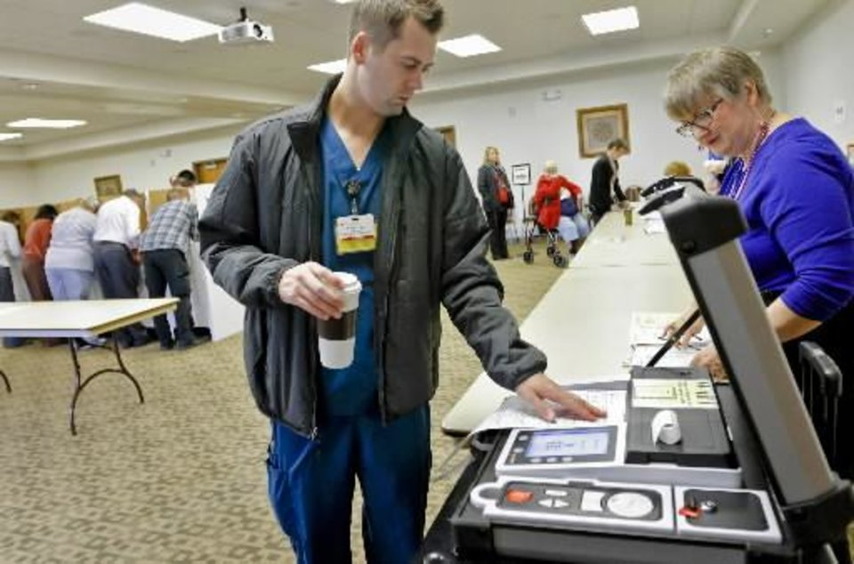 Photo - Brad Zavy cast his vote as volunteer Vicki Newby looks on during election day on Tuesday, Nov. 6, 2012, in Yukon, Oklahoma. Photo by Chris Landsberger, The Oklahoman
