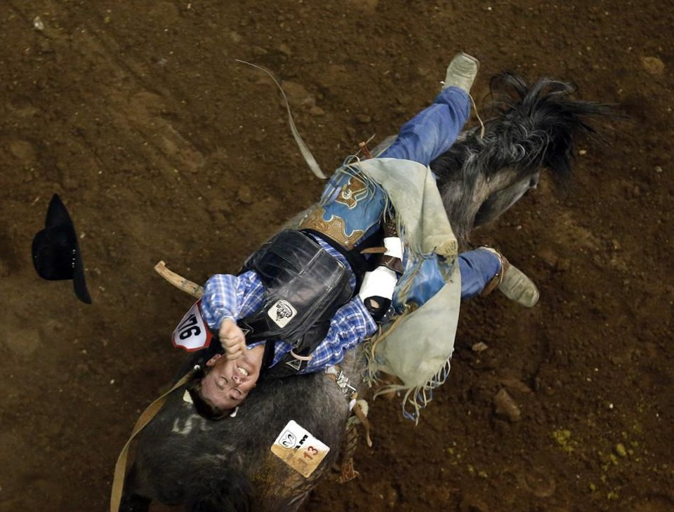 Photo -  Tyson Thompson rides during the bareback riding competition at the National Circuit Finals Rodeo at the State Fair Arena in Oklahoma City, Friday, April 5, 2013. Photo by Sarah Phipps, The Oklahoman