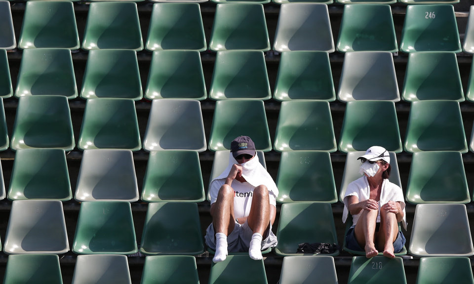 Photo - Tennis fans protect themselves from the sun during a first round match at the Australian Open tennis championship in Melbourne, Australia, Tuesday, Jan. 14, 2014.(AP Photo/Aaron Favila)