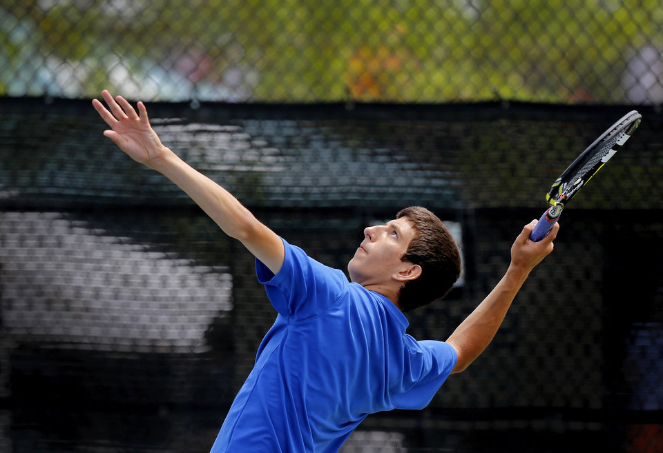 Photo - Mt. St. Mary High School's Blake Crawford during a serve to  Lucas Meacham as the pair competed in the Class 4A no. 1 singles championship match at the state championship tennis tournaments at the OKC Tennis Center on N. Portland Saturday afternoon, May 17, 2014. Crawford defeated Meacham of Crossings Christian to win the  championship. Photo by Jim Beckel, The Oklahoman