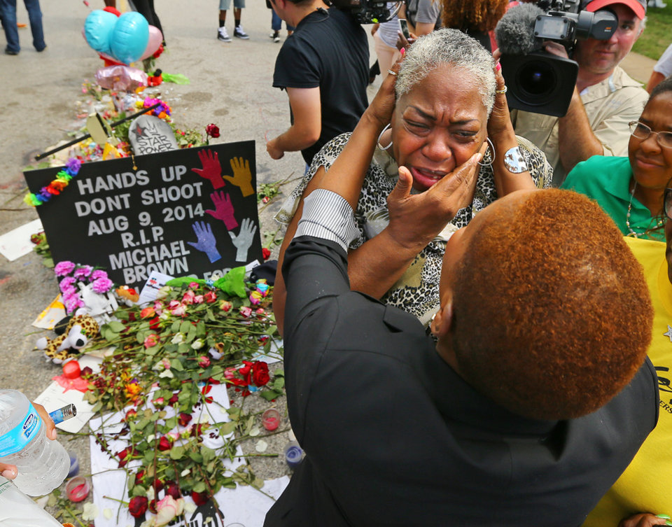 Photo - Spiritual teacher Iyanla Vanzant, right, consoles Shirley Scale, a resident at the Canfield Apartments, at the shrine to Michael Brown where he was shot and killed on Wednesday, Aug. 20, 2014, in Ferguson, Mo. Vanzant, from the