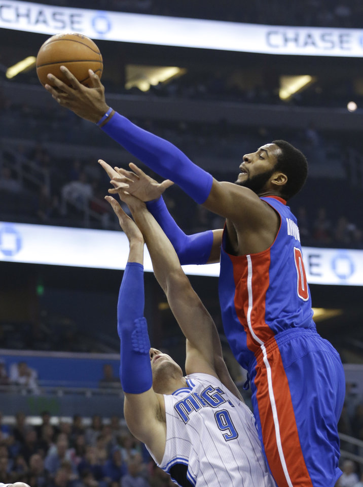 Photo - Detroit Pistons' Andre Drummond, right, shoots over Orlando Magic's Nikola Vucevic (9), of Montenegro, during the first half of an NBA basketball game in Orlando, Fla., Friday, Dec. 27, 2013. (AP Photo/John Raoux)