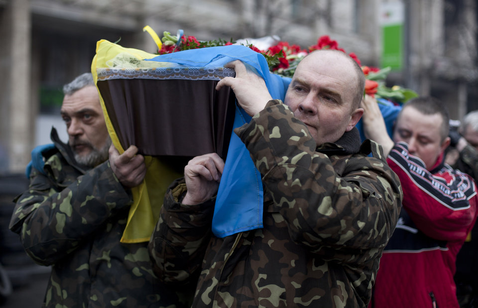 Photo - Pallbearers carry a coffin bearing the body Andryi Pozniak, 25, a self defense volunteer who was shot and killed by an unknown assailant two days ago near Kiev's Independence Square, Ukraine, Thursday, March 6, 2014. (AP Photo/David Azia)