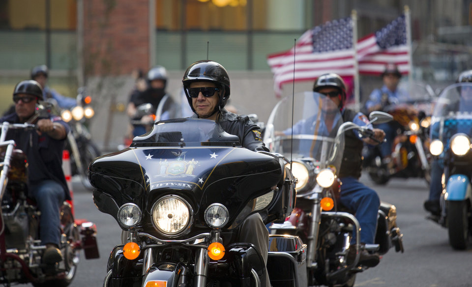 Photo - New York Gov. Andrew Cuomo rides with firefighters and first responders with the FDNY Motorcycle Club Wednesday, Sept. 11, 2013, from FDNY Rescue 1 headquarters to the World Trade Center site for the 12th anniversary of the 2001 terrorist attacks. The ride represented the firefighters who responded to the attacks on that day. (AP Photo/Craig Ruttle)