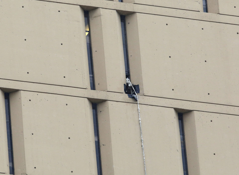 Photo - A rope dangles from a window on the back side of the Metropolitan Correctional Center Tuesday, Dec. 18, 2012, in Chicago. Two convicted bank robbers used a knotted rope or bed sheets to escape from the federal prison window high above downtown Chicago early Tuesday, a week after one of them made a courtroom vow of retribution, to federal judge. The escape occurred sometime between 5 a.m. and 8:45 a.m. when the inmates were discovered missing, Chicago Police Sgt. Mark Lazarro said. Hours later, what appeared to be a rope, knotted at six-foot intervals, could be seen dangling into an alley from a window of the Metropolitan Correctional Center approximately 20 stories above the ground. (AP Photo/M. Spencer Green)